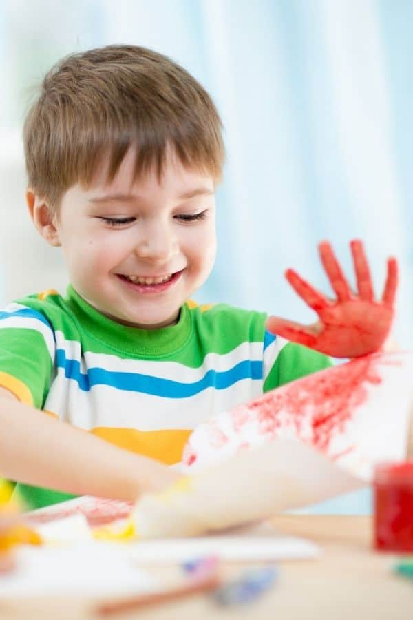 Brown haired boy finger painting at Maryville TN Daycares